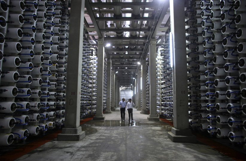 People walk in a desalination plant during its inauguration in the coastal city of Hadera, north of Tel Aviv May 16, 2010. (photo credit: NIR ELIAS / REUTERS)