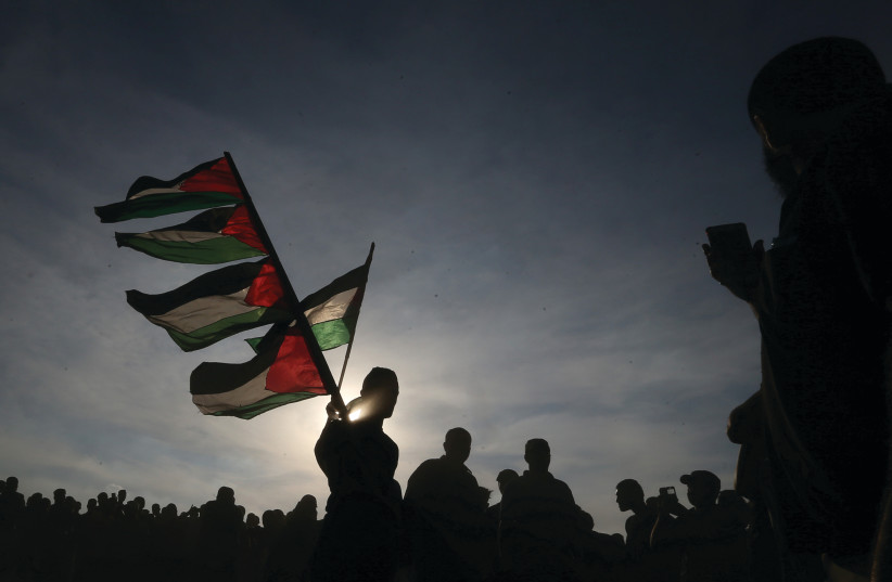 Palestinian protesters wave flag at recent events (photo credit: REUTERS)