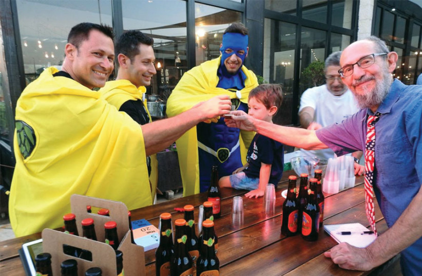 THE WRITER (right) raises a glass with 'superheroes' from Six Pack Brewing, at a recent craft beer festival. (photo credit: MIKE HORTON)