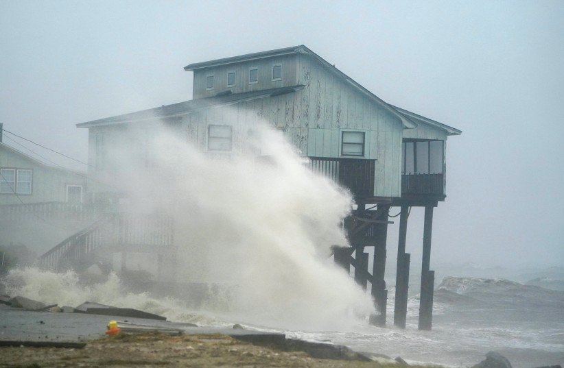 Waves take over a house as Hurricane Michael comes ashore in Alligator Point, Florida, U.S., October 10, 2018.  (photo credit: CARLO ALLEGRI/REUTERS)