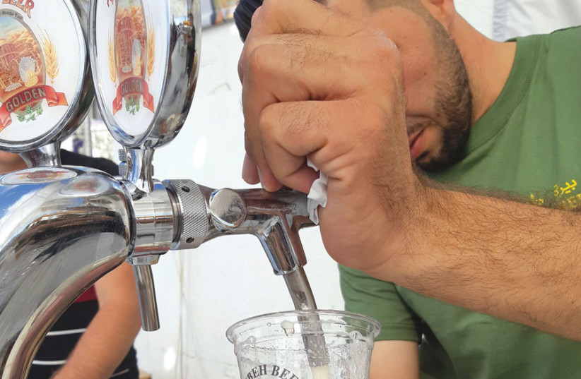 Brewer Canaan Khoury pouring at Oktoberfest (photo credit: NETANEL CHURGIN)