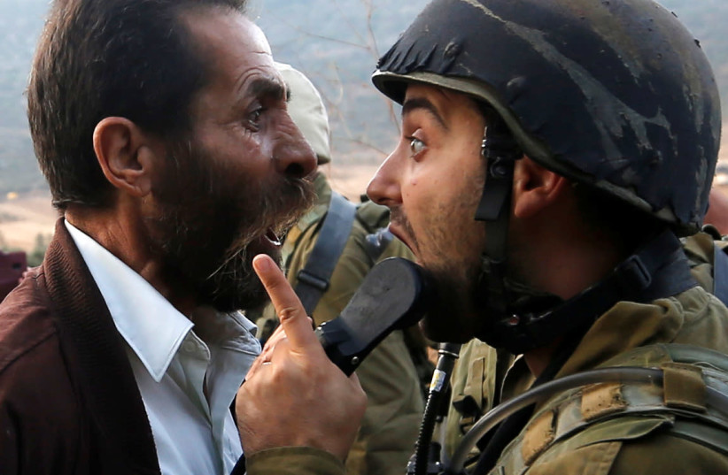 A Palestinian man argues with an Israeli soldier during clashes over an Israeli order to shut down a Palestinian school near Nablus in  West Bank October 15, 2018.  (photo credit: MOHAMAD TOROKMAN/REUTERS)