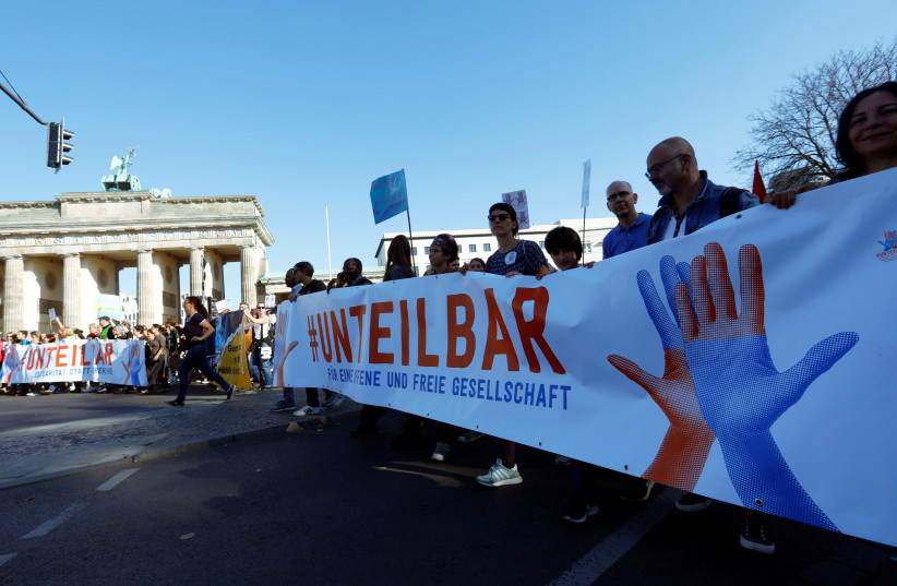 """Protesters gather to the """"#unteilbar"""", demonstration which aims to """"rise up against discrimination, poverty, racism, sexism, disenfranchisement, and nationalism"""" in Berlin, Germany, October 13, 2018 (photo credit: MICHELE TANTUSSI / REUTERS)"""