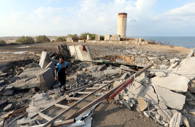 A Palestinian man inspects the scene of an Israeli air strike on a Hamas security forces site in the southern Gaza Strip October 17, 2018 (photo credit: IBRAHEEM ABU MUSTAFA / REUTERS)