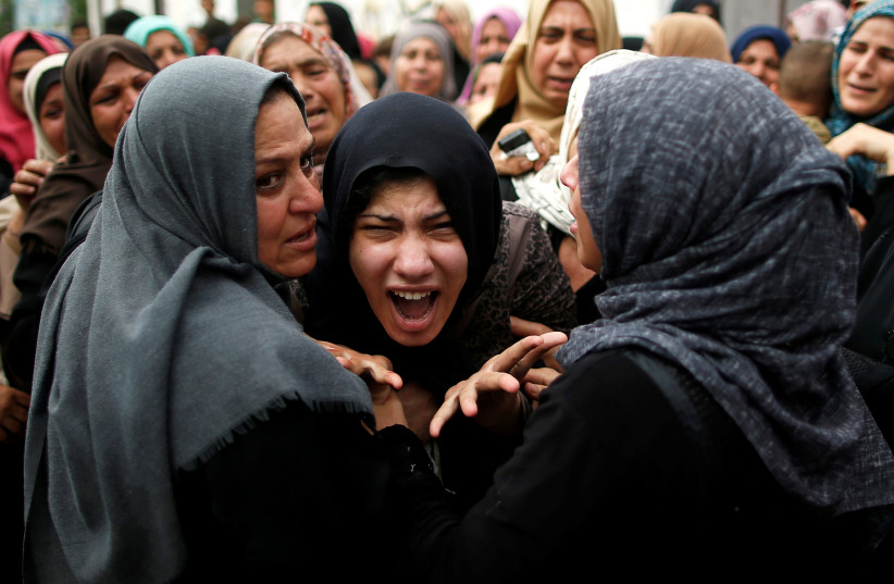 A relative of Palestinian gunman Naji al-Zaneen, who was killed in an Israeli air strike, reacts during his funeral in the northern Gaza Strip October 17, 2018 (photo credit: SUHAIB SALEM / REUTERS)