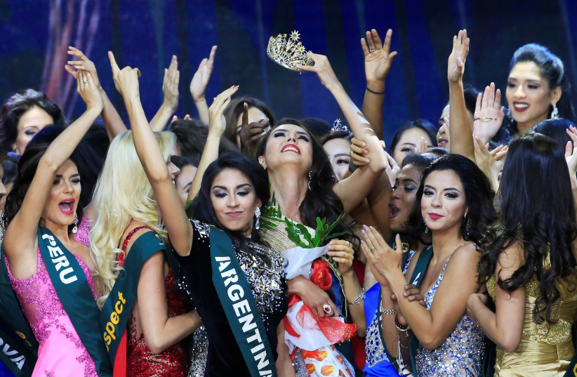 Miss Colombia Michelle Gomez (C), crowned 2016's Miss Earth Air, raises her crown while other contestants greet her (photo credit: REUTERS/ROMEO RANOCO)