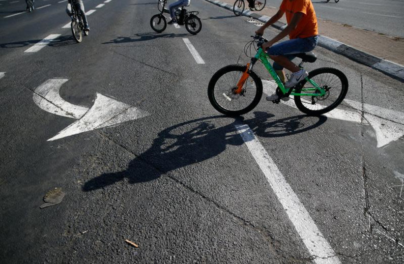 Children ride their bicycles on an empty road during the Jewish holiday Yom Kippur in Jerusalem, September 30, 2017. (photo credit: REUTERS/AMMAR AWAD)