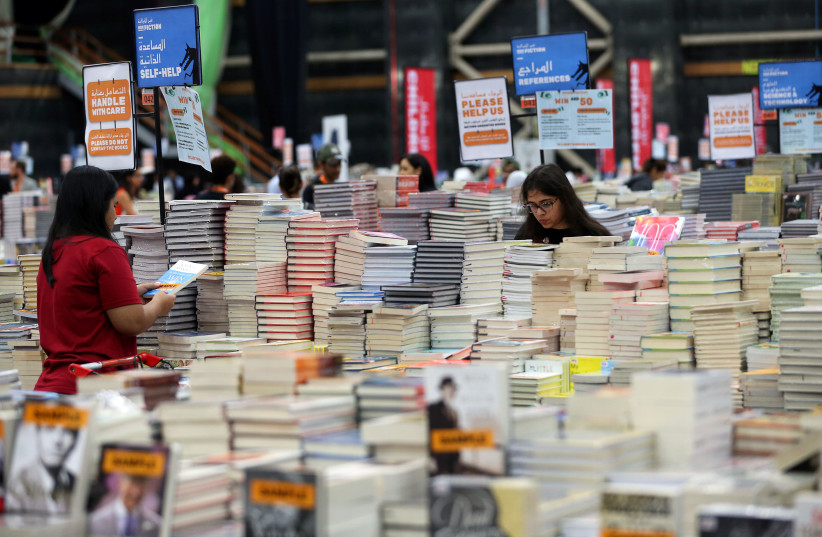 Visitors read books at the Big Bad Wolf Book Sale, which calls itself the world's biggest, hosted for the first time by Dubai, UAE October 17, 2018 (photo credit: REUTERS/SATISH KUMAR)