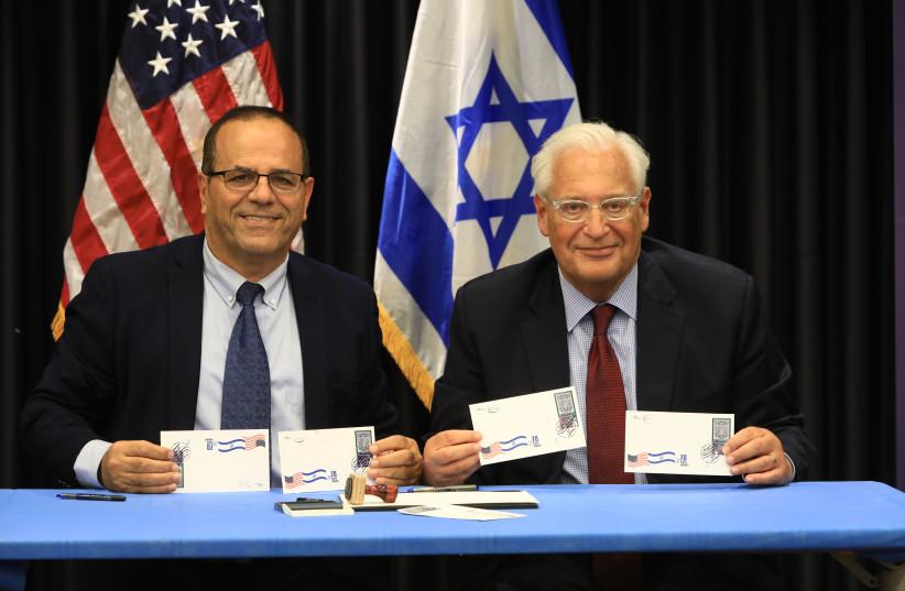COMMUNICATIONS MINISTER Ayoub Kara (left) and US Ambassador David Friedman display first day covers of new joint Israel-US postage stamp for Hanukka (photo credit: SASSON TIRAM)
