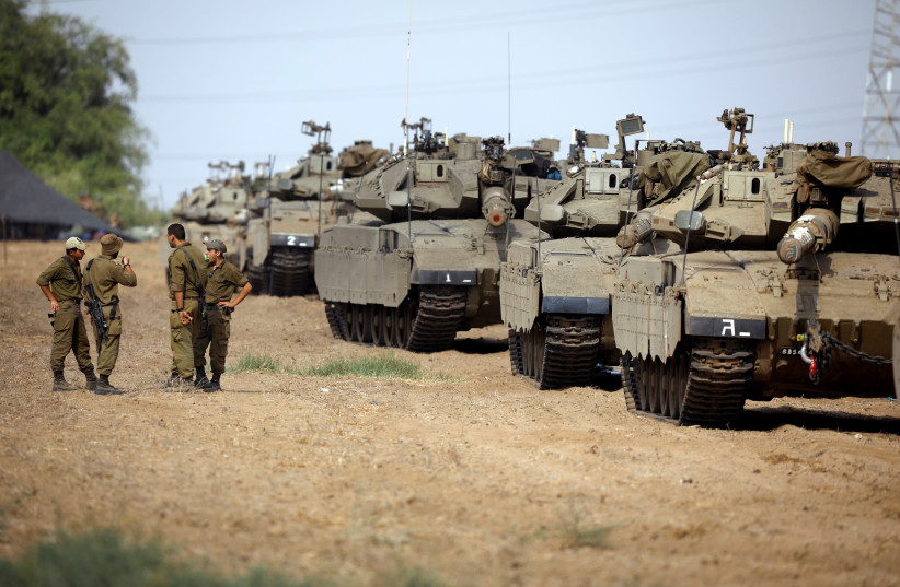 Israeli soldiers speak next to tanks as military armoured vehicles gather in an open area near Israel's border with the Gaza Strip October 18, 2018.  (photo credit: REUTERS/AMIR COHEN)