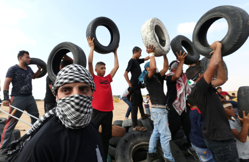 A masked Palestinian demonstrator gestures as others hold tires during a protest at the Israel-Gaza border fence in the southern Gaza Strip October 19, 2018. (photo credit: IBRAHEEM ABU MUSTAFA / REUTERS)