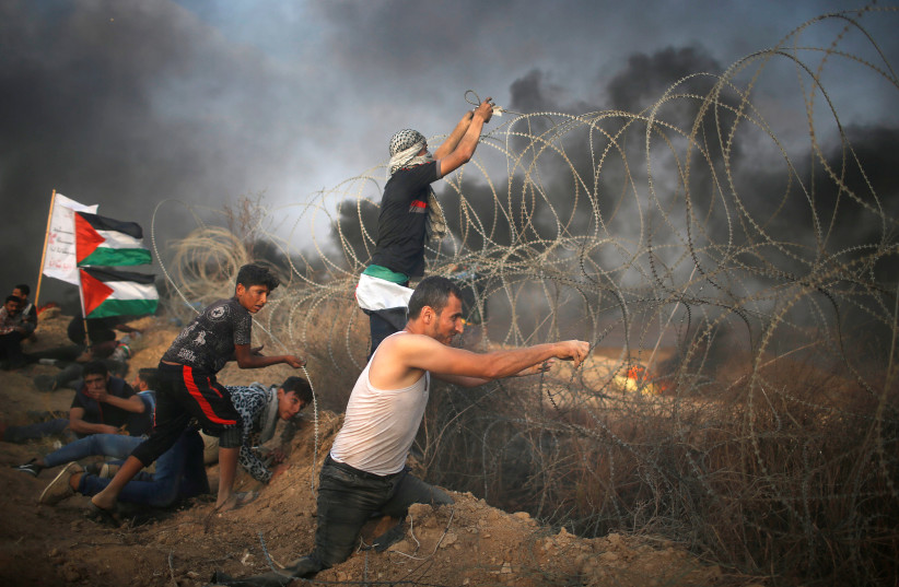 Disable Palestinian tries to remove Israeli wire during a protest at the Israel-Gaza border fence in Gaza. (photo credit: MOHAMMED SALEM/ REUTERS)