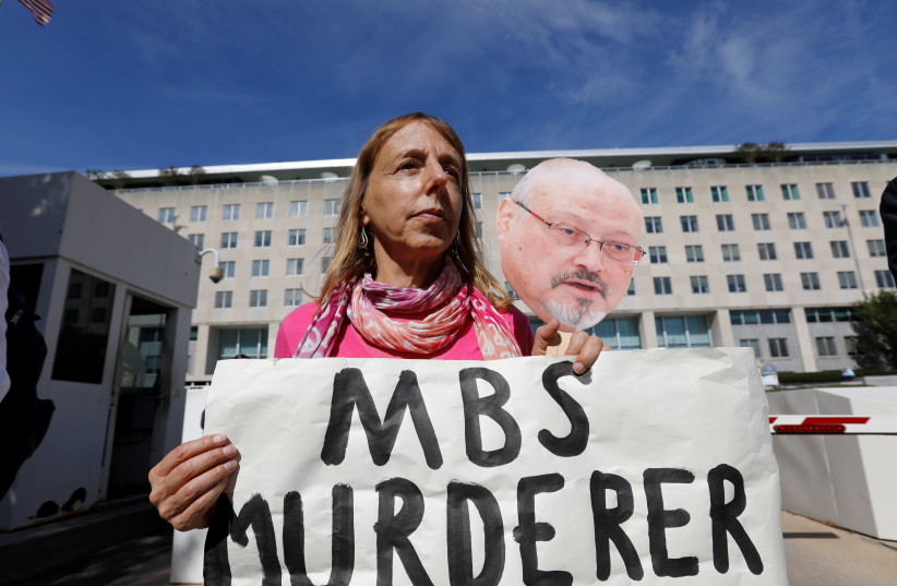 """Code Pink"" activist group co-founder Medea Benjamin participates in a demonstration calling for sanctions against Saudi Arabia and against the disappearance of Saudi journalist Jamal Khashoggi while holding a photo of Khashoggi outside the U.S. State Department in Washington, October 19, 2018 (photo credit: KEVIN LAMARQUE/REUTERS)"