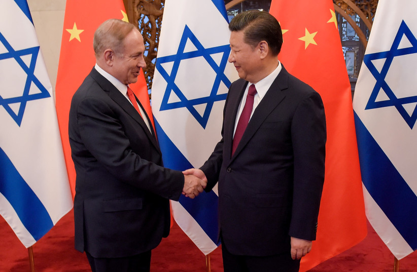 Chinese President Xi Jinping and Israeli Prime Minister Benjamin Netanyahu shake hands ahead of their talks at Diaoyutai State Guesthouse in Beijing, China March 21, 2017 (photo credit: ETIENNE OLIVEAU/POOL/REUTERS)