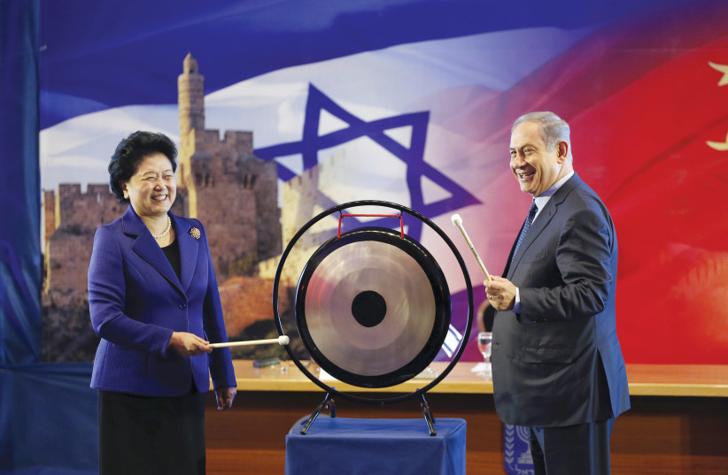 PRIME MINISTER BENJAMIN NETANYAHU and Chinese Vice Premier Liu Yandong strike a gong during the second JCIC meeting in March 2016 (photo credit: REUTERS)