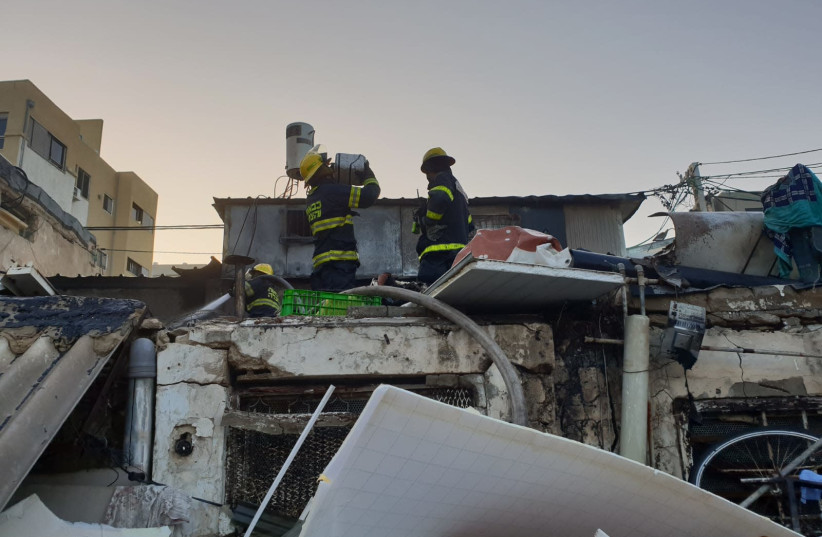 Firefighters at the burnt home of a 62-year-old woman killed in a fire in Tel Aviv's Carmel Market on Monday morning, October, 22, 2018 (photo credit: ISRAEL FIRE AND RESUCE SERVICES)