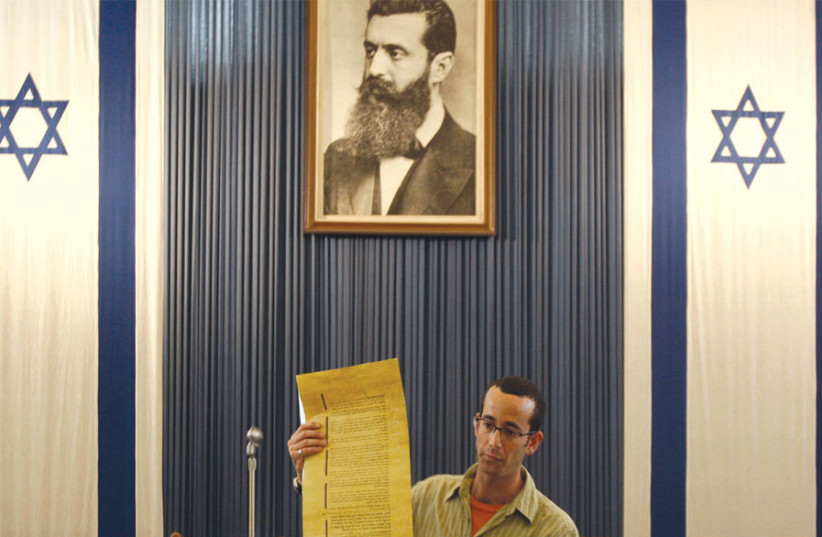 A guide stands under a portrait depicting Theodor Herzl, the father of modern Zionism, as he holds a copy of Israel's Declaration of Independence in the building where it was first read by David Ben-Gurion in Tel Aviv (photo credit: LIORA MIZRAHI / REUTERS)