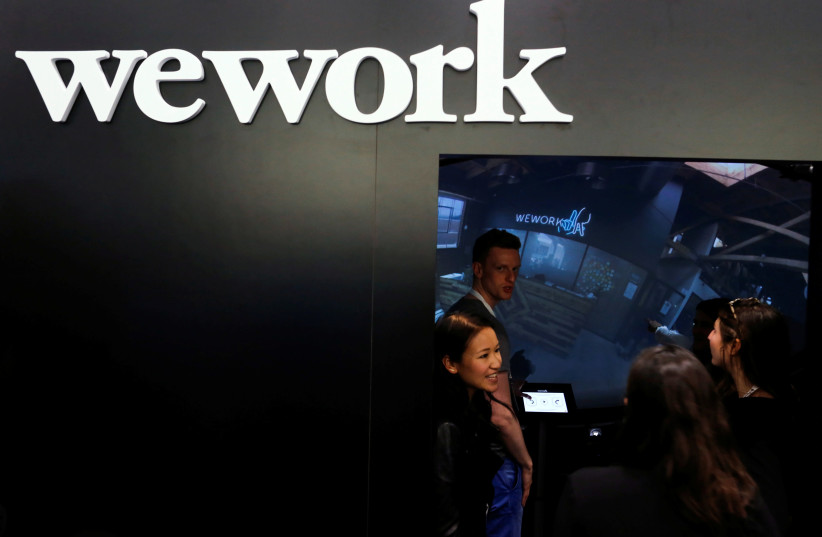 People visit the booth of WeWork as they attend the TechCrunch Disrupt event in Manhattan, in New York City, NY, U.S. May 15, 2017. (photo credit: EDUARDO MUNOZ / REUTERS)