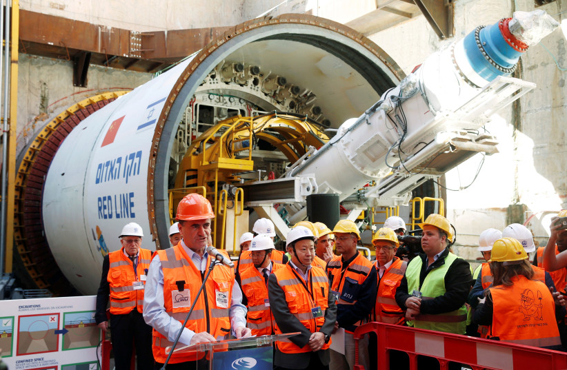 Yisrael Katz, Israel's Minister of Transport, speaks as he stands next to employees of China Railway Engineering Corporation, during an event marking the beginning of underground construction work of the light rail, using a Tunnel Boring Machine (TBM), in Tel Aviv, Israel February 19, 2017. (photo credit: BAZ RATNER/REUTERS)