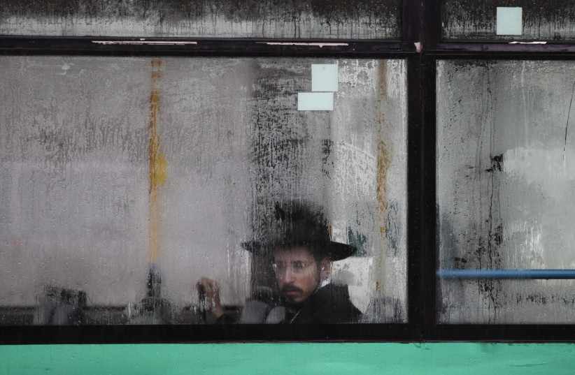 An ultra-Orthodox Jewish man looks out from a condensation-covered window of a bus in Jerusalem December 11, 2013 (photo credit: REUTERS/AMMAR AWAD)