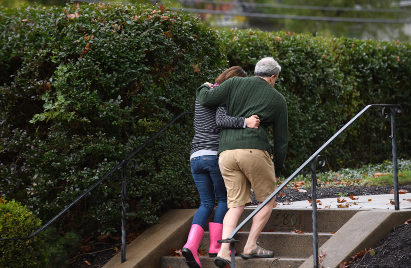 Neighbors around the corner from the site of a mass shooting at the Tree of Life Synagogue embrace one another in the Squirrel Hill neighborhood on October 27, 2018 in Pittsburgh, Pennsylvania (photo credit: JEFF SWENSEN / GETTY IMAGES NORTH AMERICA / AFP)