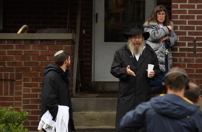 Residents talk to the media near the site of a mass shooting at the Tree of Life Synagogue in the Squirrel Hill neighborhood on October 27, 2018 in Pittsburgh, Pennsylvania (photo credit: JEFF SWENSEN / GETTY IMAGES NORTH AMERICA / AFP)
