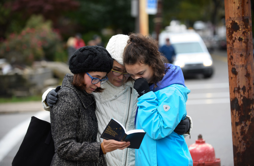 Tammy Hepps, Kate Rothstein and her daughter, Simone Rothstein, 16, pray from a prayerbook a block away from the site of a mass shooting at the Tree of Life Synagogue in the Squirrel Hill neighborhood on October 27, 2018 in Pittsburgh, Pennsylvania (photo credit: JEFF SWENSEN / GETTY IMAGES NORTH AMERICA / AFP)