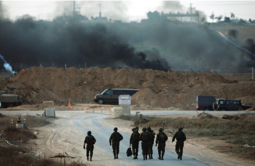 SOLDIERS WALK toward the border with the Gaza Strip (photo credit: REUTERS)