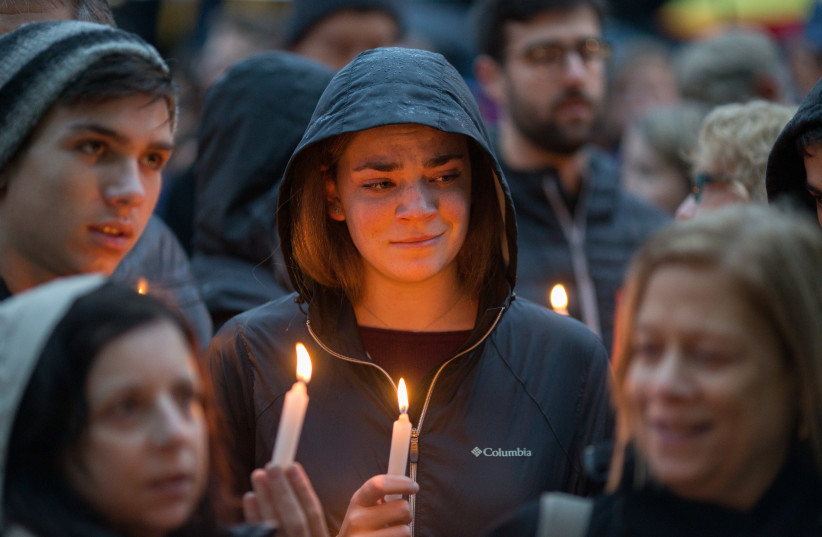 People hold a vigil for the victims of Pittsburgh synagogue shooting in Pittsburgh Pennsylvania (photo credit: REUTERS/JOHN ALTDORFER)