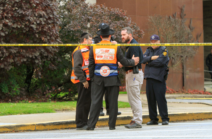 Police officers guarding the Tree of Life synagogue following shooting at the synagogue, speak with men in orange vest from a Jewish burial society in Pittsburgh, Pennsylvania, US, October 27, 2018 (photo credit: REUTERS/JOHN ALTDORFER)