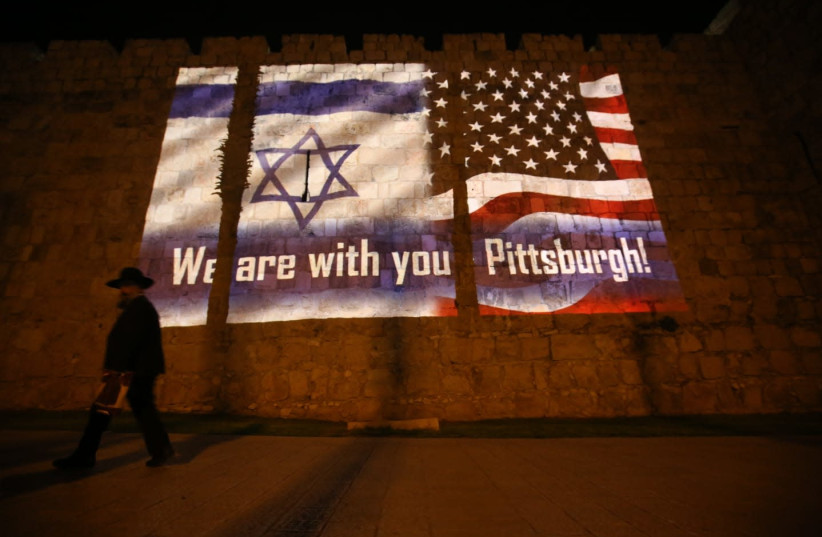 An Israeli and an American flag are projected onto Jerusalem's Old City walls near Jaffa Gate in solidarity with the victims of the shooting attack in Pittsburgh (photo credit: MARC ISRAEL SELLEM/THE JERUSALEM POST)