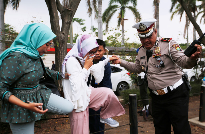 DATE IMPORTED: October 29, 2018 A policeman helps a woman who is a relative of a passenger of Lion Air flight JT610 that crashed into the sea, as she arrives at a crisis center at Soekarno Hatta International airport near Jakarta, Indonesia, October 29, 2018. (photo credit: REUTERS/WILLY KURNIAWAN)