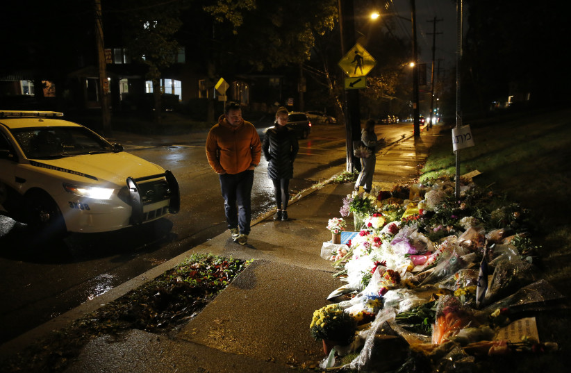 Mourners visit a makeshift memorial outside the Tree of Life synagogue, a day after 11 Jewish worshippers were shot dead in Pittsburgh, Pennsylvania, October 28, 2018 (photo credit: CATHAL MCNAUGHTON/REUTERS)