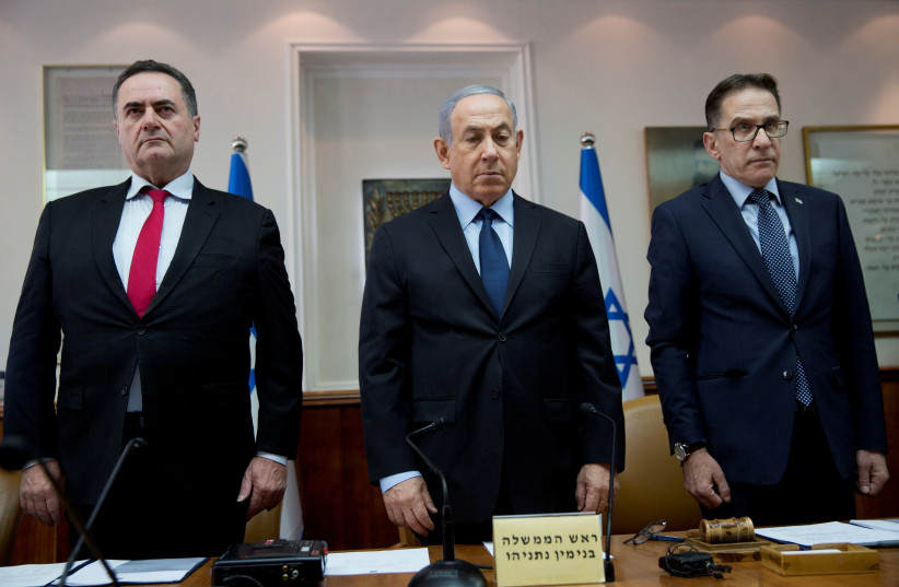 Israeli Prime Minister Benjamin Netanyahu (C), Transportation and Intelligence Minister Yisrael Katz (L), and Cabinet Secretary Tzachi Braverman stand for a moment of silence to honour the victims of a synagogue shooting in Pittsburgh, during the weekly cabinet meeting in Jerusalem October 28, 2018 (photo credit: ODED BALILTY/POOL VIA REUTERS)