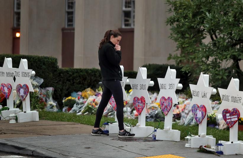 A woman reacts at a makeshift memorial outside the Tree of Life synagogue following Saturday's shooting at the synagogue in Pittsburgh, Pennsylvania, U.S., October 29, 2018 (photo credit: CATHAL MCNAUGHTON/REUTERS)