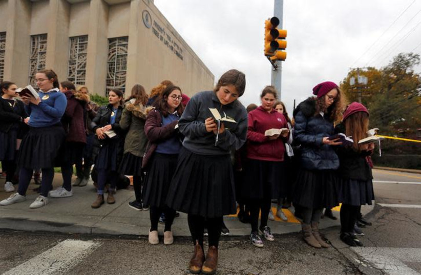 Pupils from the Yeshiva Girls School pray outside the Tree of Life synagogue following Saturday's shooting at the synagogue in Pittsburgh, Pennsylvania, U.S., October 29, 2018 (photo credit: CATHAL MCNAUGHTON/REUTERS)
