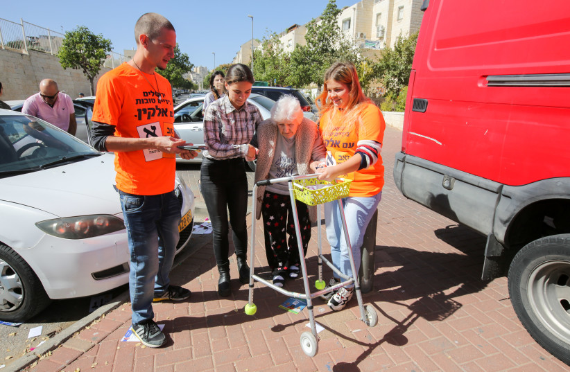 An elderly lady is helped by campaign volunteers  (photo credit: MARC ISRAEL SELLEM/THE JERUSALEM POST)
