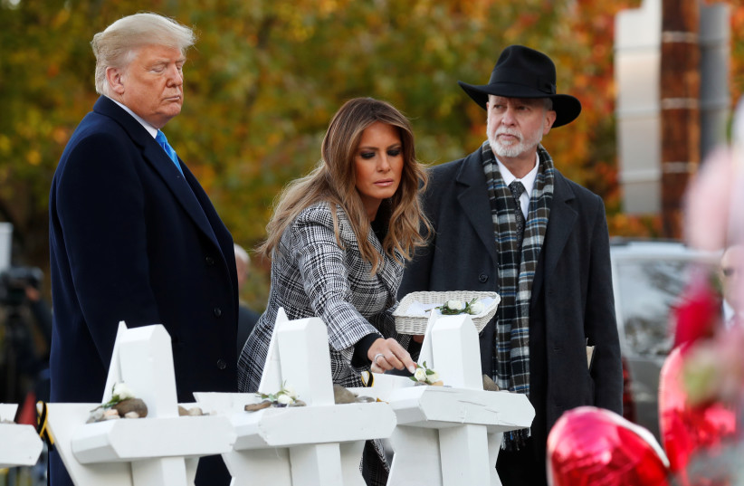 U.S. President Donald Trump and first lady Melania Trump stand with Rabbi Jeffrey Myers as they place stones at a makeshift memorial outside the Tree of Life synagogue in the wake of the shooting at the synagogue where 11 people were killed and six people were wounded in Pittsburgh, Pennsylvania,  (photo credit: KEVIN LAMARQUE/REUTERS)