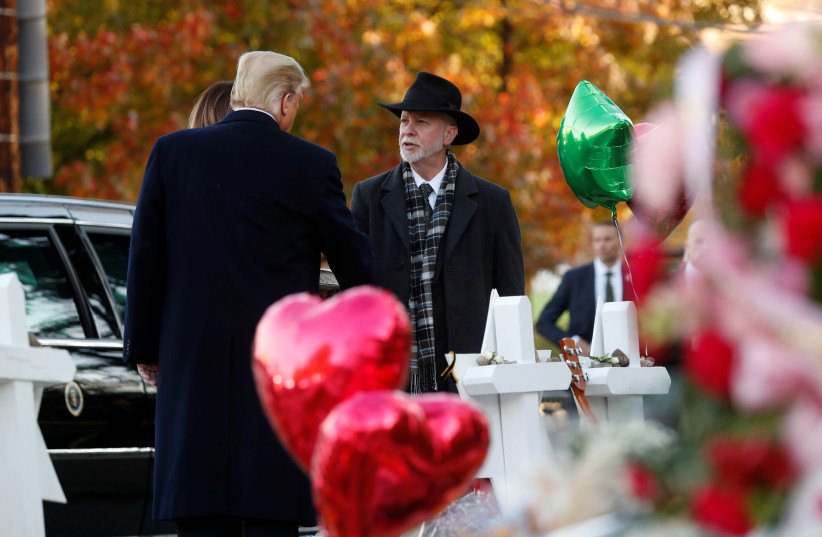 U.S. President Donald Trump talks with Tree of Life Synagogue Rabbi Jeffrey Myers as they stand at a makeshift memorial to the victims outside the synagogue where a gunman killed eleven people and wounded six during a mass shooting in Pittsburgh, Pennsylvania, U.S., October 30, 2018.  (photo credit: KEVIN LAMARQUE/REUTERS)