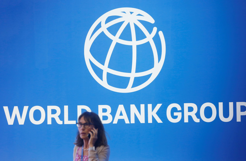 A participant stands near a logo of World Bank at the International Monetary Fund - World Bank Annual Meeting 2018 (photo credit: REUTERS/JOHANNES P. CHRISTO)