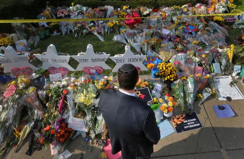 A man prays at a makeshift memorial outside the Tree of Life synagogue following Saturday's shooting at the synagogue in Pittsburgh, Pennsylvania, U.S., October 31, 2018 (photo credit: CATHAL MCNAUGHTON/REUTERS)