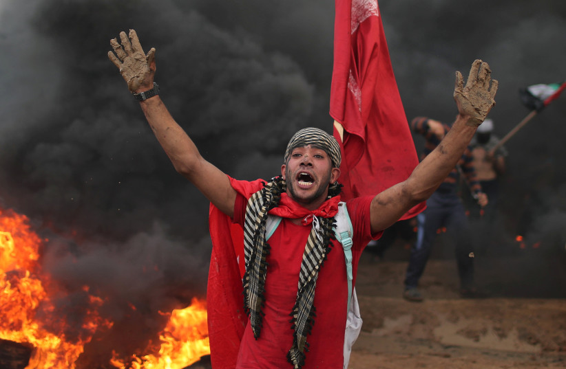 A Palestinian demonstrator reacts during a protest calling for lifting the blockade on Gaza, at the Israel-Gaza border fence in Gaza October 26, 2018 (photo credit: MOHAMMED SALEM/REUTERS)