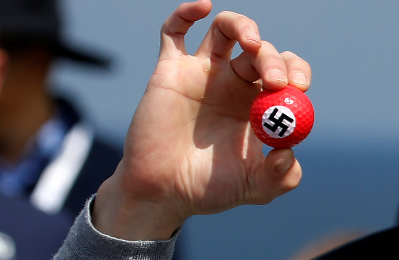 A protester holds up golf balls with a swastika as he is removed from a press conference by Republican presidential candidate Donald Trump at Turnberry Golf course in Turnberry, Scotland, June 24, 2016.  (photo credit: CARLO ALLEGRI/REUTERS)