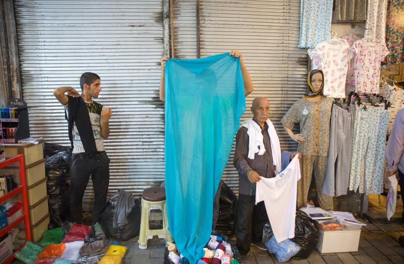 An Iranian vendor sells clothes at the Grand Bazaar in the center of Tehran, Iran, August 2, 2017 (photo credit: NAZANIN TABATABAEE YAZDI/ TIMA VIA REUTERS)