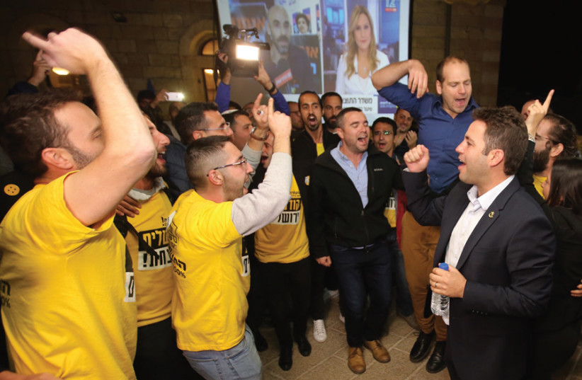 Ofer Berkovitch (right) and some supporters on election day, celebrating the news he would be moving on to the second round. (photo credit: MARC ISRAEL SELLEM)