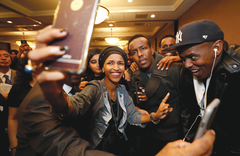 DEMOCRATIC CONGRESSIONAL candidate Ilhan Omar takes a selfie with supporters after appearing at her election party.  (photo credit: REUTERS)