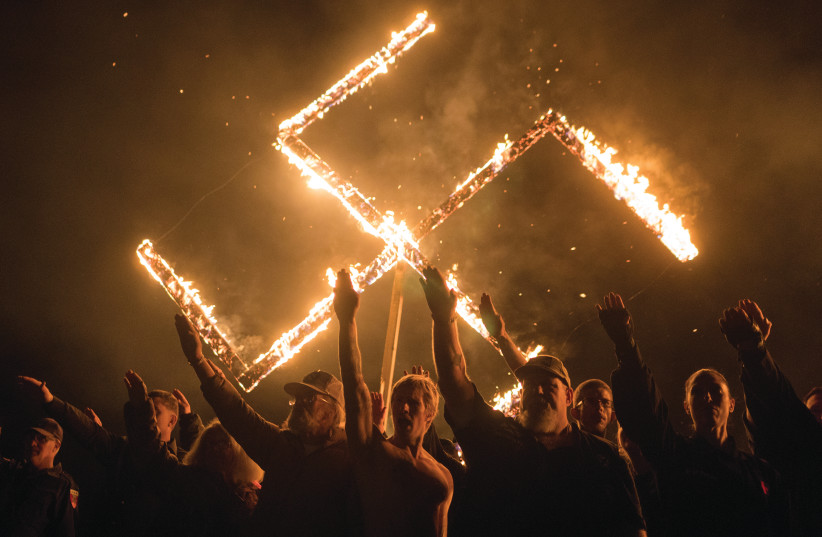 SUPPORTERS OF THE National Socialist Movement give Nazi salutes while taking part in a swastika-burning in Georgia in April.  (photo credit: GO NAKAMURA/REUTERS)