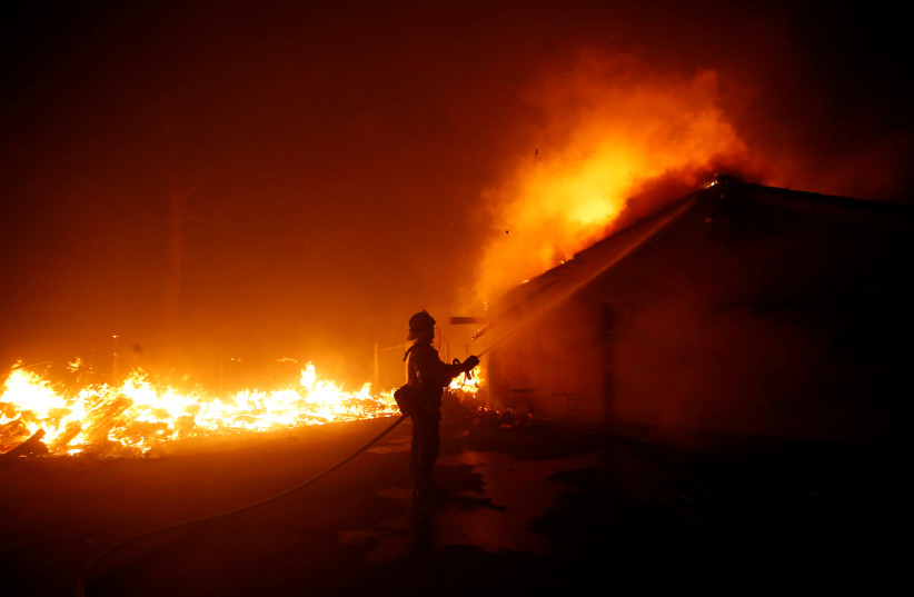 A firefighter battles the Woolsey Fire in Malibu, California, U.S. November 9, 2018. The fire destroyed dozens of structures, forced thousands of evacuations and closed a major freeway.  (photo credit: ERIC THAYER/ REUTERS)
