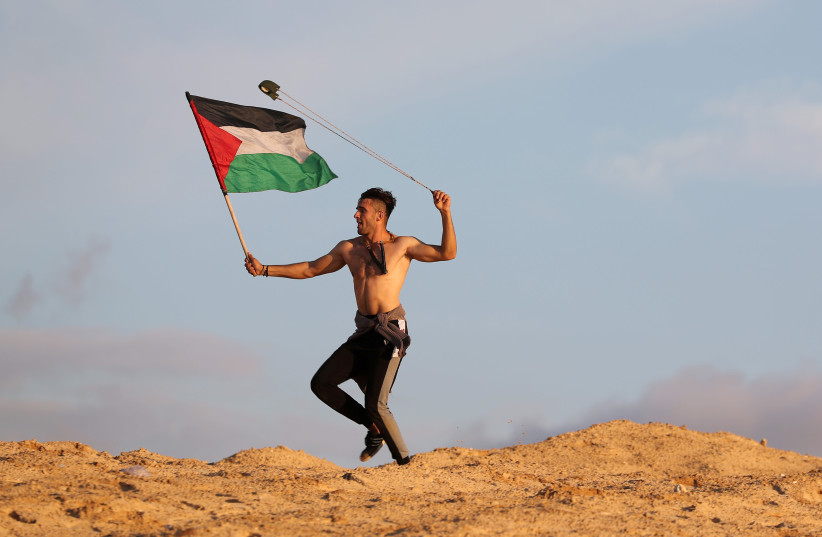 A demonstrator holding a Palestinian flag uses a sling to hurl stones at Israeli troops during a protest calling for lifting the Israeli blockade on Gaza, at the beachfront border with Israel, in the northern Gaza Strip November 5, 2018 (photo credit: MOHAMMED SALEM/REUTERS)