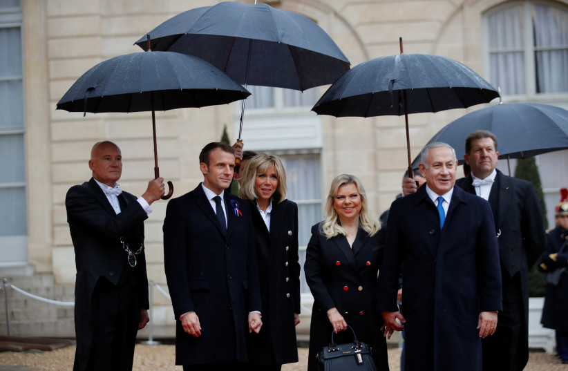 French President Emmanuel Macron and his wife Brigitte Macron welcome Israel Prime Minister Benjamin Netanyahu and his wife Sara at the Elysee Palace as part of the commemoration ceremony for Armistice Day, 100 years after the end of the First World War, in Paris, France, November 11, 2018. (photo credit: PHILIPPE WOJAZER/REUTERS)